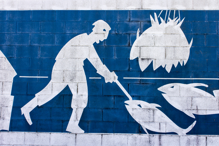 Ribadeo, Spain. Blue and white brick mosaic painting with a fisherman and some fishes and