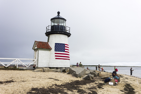 Nantucket, Massachusetts. Brant Point Light, a lighthouse located on the harbor of Nantucket Island, with several people fishing and an American flag Editorial