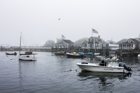 Nantucket island, Massachusetts. Views of the Nantucket harbor with boats and traditional wooden houses on a misty summer day Editorial