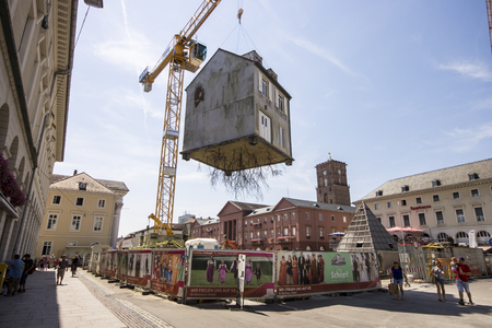 Karlsruhe, Germany. Suspended house hanging from a construction crane in the Marktplatz by Argentinian artist Leandro Erlich, an artwork called Pulled by the Roots