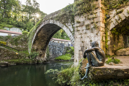 Lierganes, Spain. The Puente Viejo (Old Bridge), with the statue of the Hombre Pez (Fish-man), an entity which belongs to the mythology of Cantabria, named Francisco de la Vega Casar Editorial