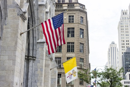 New York City. Flags of the United States of America and the Vatican City State hanging from the main facade of St. Patricks Cathedral in Manhattan