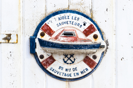 An Aidez les Sauveteurs (help the lifeguards) sign at a wooden door, from the SNSM, a French voluntary organisation that saves lives at sea around the French coast