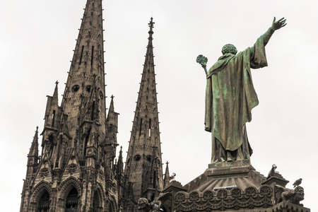 Clermont-Ferrand, France. Statue of Pope Urban II (1035-1099) overlooking the towers of the Gothic Cathedral of Our Lady of the Assumption