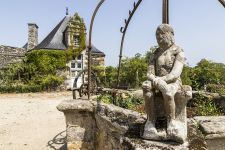 Rochefort-en-Terre, France. A well with a statue at Rochefort, one of the most beautiful towns in Brittany (Bretagne) Stock Photo