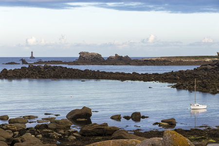 Porspoder, France. Rocky landscape in the coast of Brittany (Bretagne) at dawn on a beautiful summer day, with a boat and a lighthouse