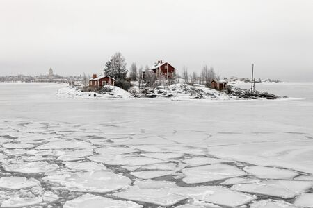 Red wooden house on an island covered in snow during winter in Helsinki, Finland