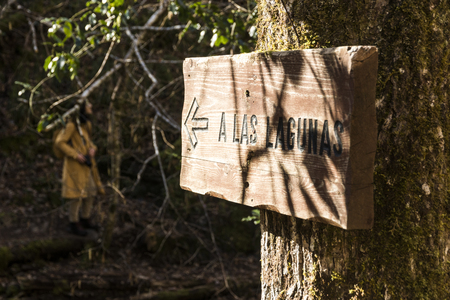 Asturias, Spain. Signpost with A Las Lagunas (to the lakes) in the Muniellos Nature Reserve (Reserva natural integral), with a woman in the background