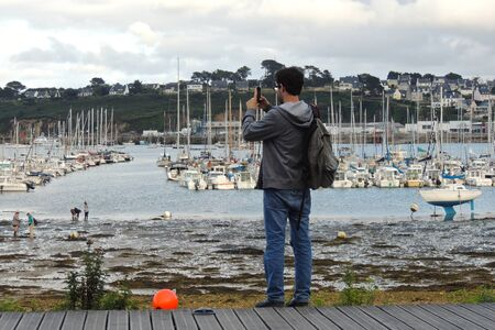Camaret-sur-Mer, France. Young photographer in fron of the boats and ships of the marina
