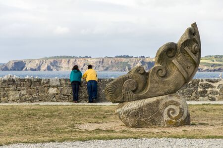 Camaret-sur-Mer, France. Two women looking at the coast from the Sillon with a sculpture in the foreground