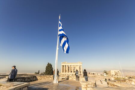 Athens, Greece. Views of the Acropolis on a sunny summer morning, with the Parthenon, Erechtheion, and a waving flag of Greece