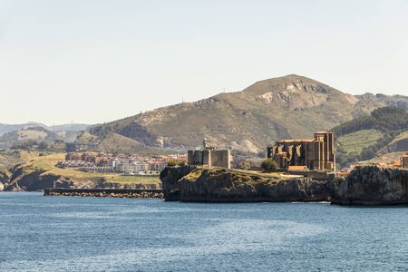 Castro Urdiales, Spain. Views of Santa Maria de la Asuncion Church and Castle of Santa Ana lighthouse from the Cementerio de Ballena