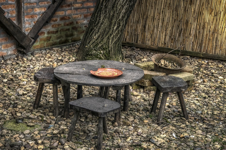 A little wooden table and three three-legged chairs, typical for Serbian countryside