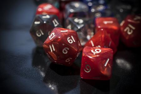 Een set rode en transparante RPG-dobbelstenen op een zwarte tafel
