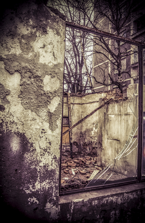 A broken window on an abandoned derelict house Stock Photo