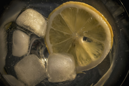 A close-up photo of cubes of ice and a piece of lemon in a glass of water