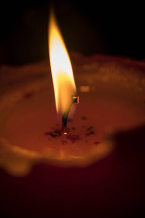 A close-up photo of a lit red candle Stok Fotoğraf