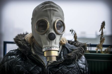 A middle aged woman with a gas mask with fog and pollution in the background