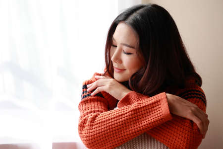 close up portrait of a young beautiful Asian woman wearing a sweater at home. She felt relaxed in the room with the morning sunny. Stock fotó