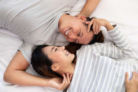 The Close-up of the happy an Asian couple is lying in bed together. They meet each other's eyes showing love.
