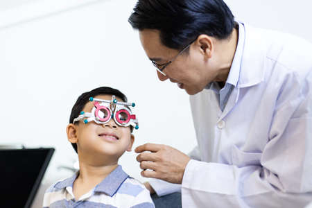 An Asian ophthalmologist examines the child's vision. An optometrist examines a child's eyesight using a Trial Frame. The boy patient visits an ophthalmology clinic. They have smiling faces Standard-Bild