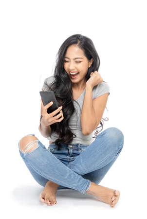 Portrait of An Asian woman sits on the floor. She is surprised by the promotions shown on the smartphone screen. She is excited and happy. Isolated on white background