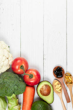 Vegetables and vitamins placed on a white wooden table.Healthy food concept, Top view, space copy Stock fotó