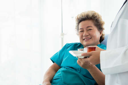 Portrait of a young beautiful Asian doctor who provided medicine to woman elderly patients in bed in the hospital. Their faces are smiling. Health care concept And health insurance