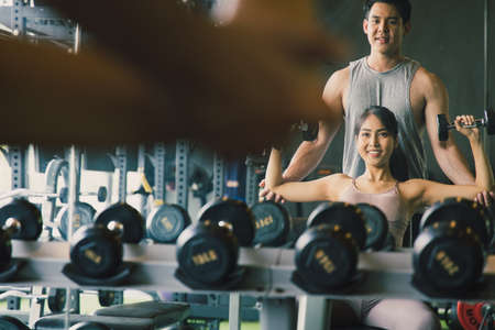 The personal trainer helps Asian women with shoulder workout in gym. They look at themselves in a large mirror. Concept Exercise for good shape