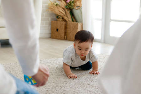 Asian baby crawl towards their parents. His face is smiling.