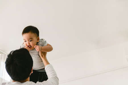 An Asian father holds his child up in the sky. His baby face was smiling with a white background.