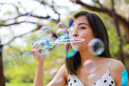 Outdoor autumn summer portrait of asian young beautiful happy woman making soap bubbles in park. Her Joyous happy in white dress. Holiday relaxation ideas Stock Photo