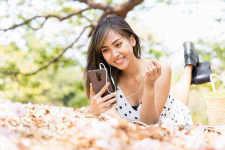 Young Asian women are relaxing on summer holidays by listening to music on their smartphone headphones in park. She has a smiling and happy face.