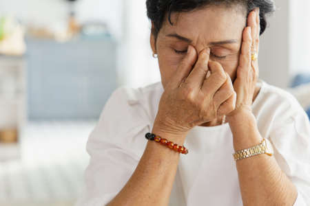 An elderly Asian woman uses her hand to grasp the head. Old women have dizziness and headache due to stress. She has a congenital disease. The health concept of retirement