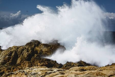 A strong wave hits the rocks of a cliff. Relating to the sea, travel, coast, shore, weather