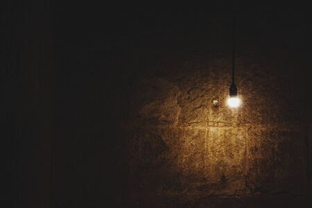 Lit light bulb hanging from the ceiling and lighting up a brown wall. Relating to minimalism, mystery and antiquity.