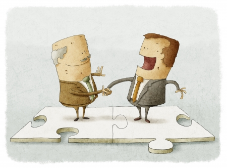 two business people on a puzzle make a handshake
