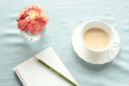 note book: t� al latte con il taccuino sul tavolo per un'immagine di studio