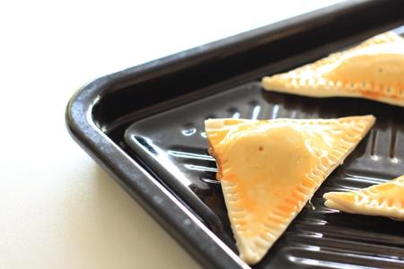 meat pie: raw meat pie in triangle shape on baking plate