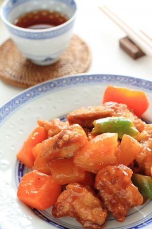 chinese cuisine, sweet   sour spareribs with vegetable and fruit and tea Фото со стока