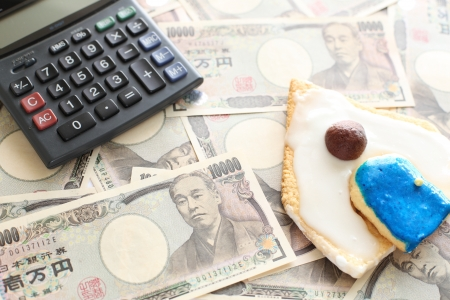 housing loan: calculator and money with house shaped cookie for housing loan image Stock Photo