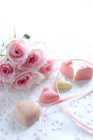 elegant pink roses on wrapping paper with heart shaped chocolate photo