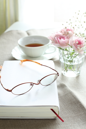 reading glasses on book with tea and flower  photo