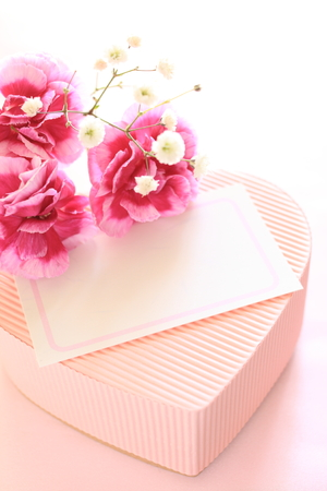 Pink carnations on heart shape gift box with greeting card