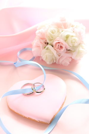 wedding rings on pink icing cookie in heart shape with flower bouquet of wedding image