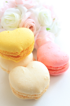 heart shaped macaron with wedding bouquet on background photo