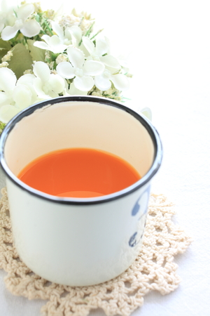 carrot juice: Carrot juice in tin cup with flower