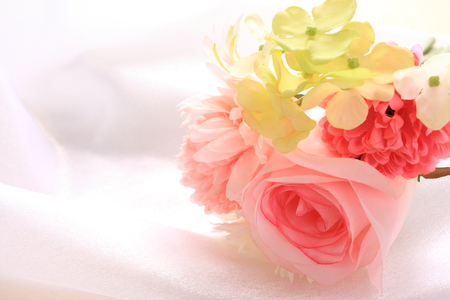 pastel flowers: Artificial flower on satin Stock Photo