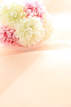 still life flowers: artificial flower on pink satin fabric Stock Photo