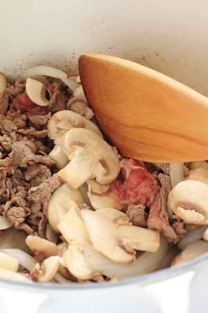 stiring: sliced mushroom and beef stir fried for stew cooking image